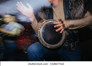 Close up of musician in extravagant native clothes, furry jacket and jeans, plaing on hand drum during concert. Motion blured surroundings. Cropped. No head. Percussion rings on his fingers.