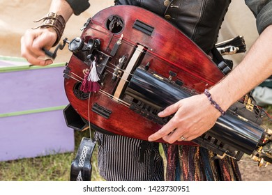 Close up of musician playing electric mandolin dressed in renaissance period costume at a Renaissance Fair.
