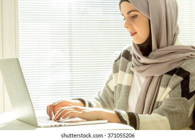 Close Up of muslim business woman typing on laptop.