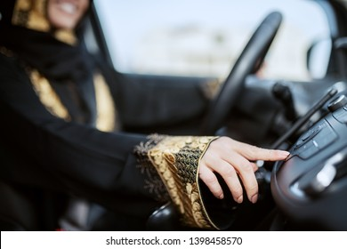 Close up of muslim woman dressed in traditional wear driving car and changing radio station.