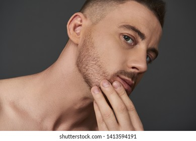 Close up of naked attractive Caucasian guy posing for camera. He is touching his stubble against gray background. Body care concept