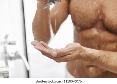 Close up of a naked man putting shower gel from a bottle while having a shower