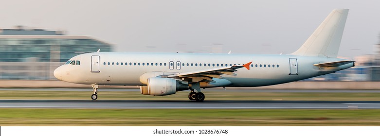 Close narrow-body passenger airplane taxing on runway for take off at beautiful sunset in summer, side view, in motion/ Vacation, aviation, travel, trip - concept/ blurred background/ Departure board
