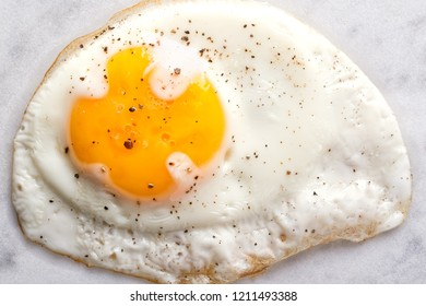 Close up of a natural looking sunnyside up pan fried egg with salt and coarse ground pepper.