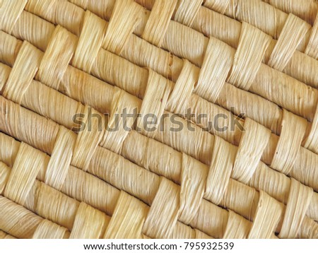 Close up of natural woven mat showing detail of the woven pattern. Dried leaves are used to create the design. Background texture.