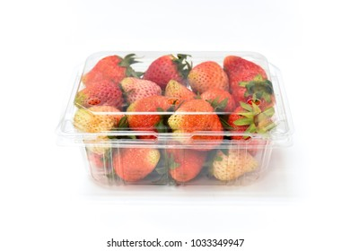 Close up near ripe red strawberry in plastic transparency pack, isolated on white background