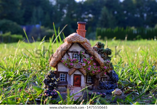 Close up of a neatly decorated cottage house replica made out of clay and plastic resembling a rural dwelling located on a grass lawn or field with dense forest or moor visible in the background