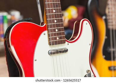 Close up of neck, body, pickup, strings, and pick guard on a modern, vintage, classic electric guitar.