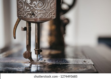 Close up of the needle and details on a vintage sewing machine.