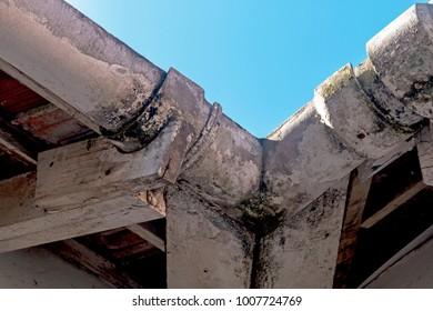 Close up of neglected vintage mouldy asbestos corner gutters and peeling wooden trusses on residential building