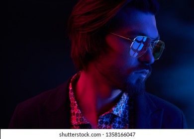 Close up neon light portrait of handsome male model with dark medium length hair, mustaches and beard in sunglasses, weared in dark jacket and floral shirt.