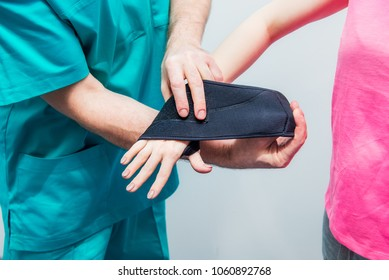Close up Neurologist doctor, therapist puts on wrist retainer on young female patient's hand. Pain treatment. Neurology, Osteopathy, chiropractic. Selective focus. space for text