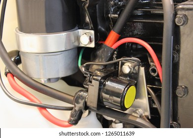 Close up new electric starter, starter relay and black and red power wires on outboard motor engine