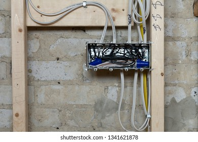Close up of a new electrical installation with wires connected into a metal box in a renovation site in Ontario, Canada. The wires are stapled to the wooden studs.
