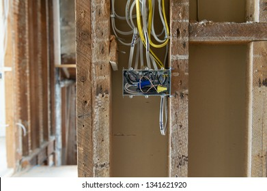 Close up of a new electrical installation with wires connected into a metal box in a residential renovation site in Ontario, Canada. The wires are stapled to the wooden studs.