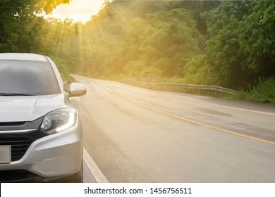Close up new front of silver car  parked on street at parking lane with morning sunlight while driving pass through the forest, safety travel holiday transportation with car in a nature concept
