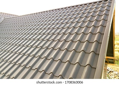 Close up of new house roof structure covered with metal tile sheets.