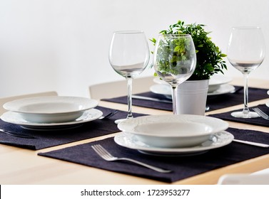 Close up new white porcelain tableware plates on purple place mats and empty wine glasses ready for dinner. Table settings wait for guests at home or restaurant, artificial potted plant for decoration