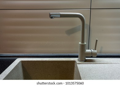 Close up new yellow metal faucet in a kitchen.
