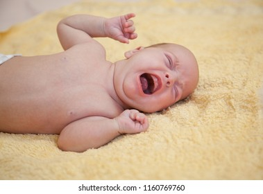 Close up of newborn crying baby on yellow towel