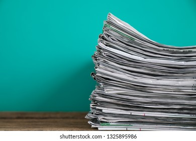 close up newspapers folded and stacked on the table with green background