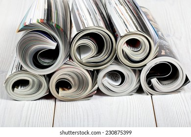 Close up of newspapers and magazine on white wood floor