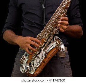 Close up of nice saxophone, silver one with someone touching it