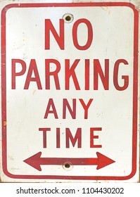 A close up of a No Parking Anytime Sign with arrows.