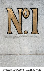Close Up of a No1 Door Number Painted in Gold on a Stone Wall