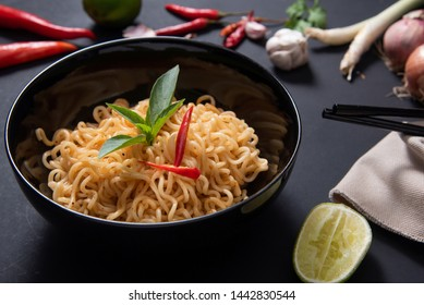 Close up noodles spicy in the bowl with ingredient on black wooden background.