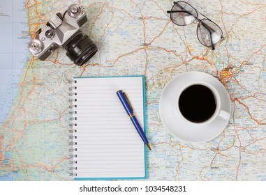 Close up of notebook, pen, photocamera and glasses and touristic map on table. Travel, trip vacation, tourism mockup. Empty space you can place your text or information.