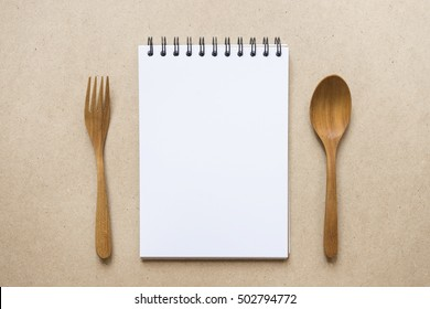 close up notebook, spoon and fork on brown paper background