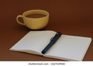 close up notebook for text and cup of hot coffee on brown background