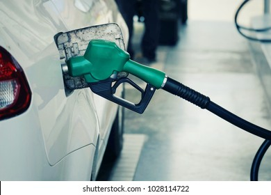 close up nozzle  fuel fill oil into car  tank at pump gas station, saving money and energy for transport, manage for success business concept, vintage tone