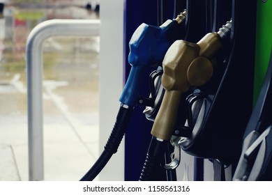 close up nozzle fuel for fill oil into car or motorcycle tank at pump gas station, transport energy, transportation business technology concept, vintage tone