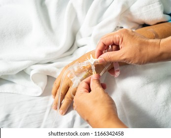 Close up nurse hand adjust three way of iv set for fluid intravenous drop saline drip on white hospital bed background in the hospital room.Medical treatment emergency patient.