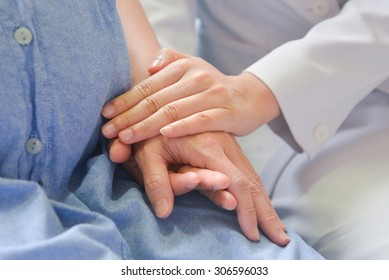 Close up of a nurse touching hand of a patient in hospital