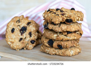 Close up oatmeal cookies with raisins on a wooden board.