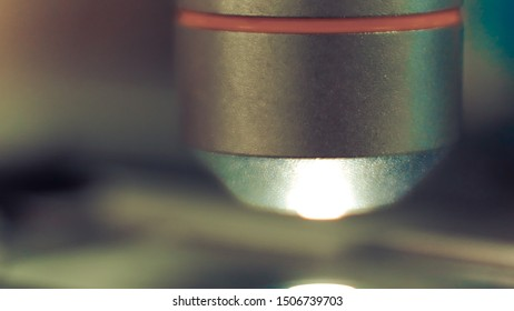 Close up objective lens of microscope on blur background.
