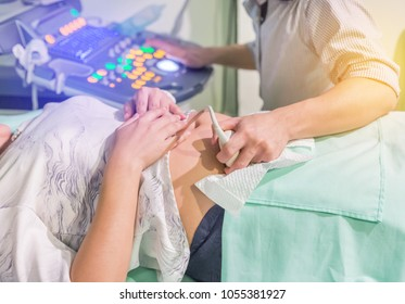 Close up obstetrician diagnostics examining pregnant woman with ultrasound scan equipment at the hospital laboratory