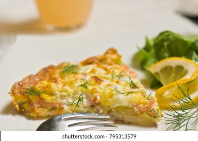 Close up ofa slice of warm, baked, homemade smoked salmon frittata with dill, slice of lemon, lettece an artisan fork and a glass of grapefruit juice
