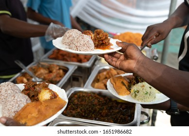 A close up of Ofada rice served with moin moin, egg and obe din din sauce - Shutterstock ID 1651986682