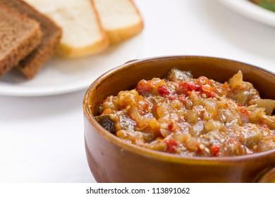 Close up off eggplant caviar in the rustic bowl. Ukrainian cuisine.