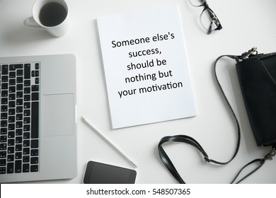 """Close up of an office desk with laptop, hand bag and female office supplies. Photo with motivational text """"Someone else is success should be nothing but your motivation"""". Business concept photo"""