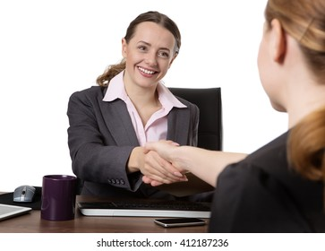 Close up office shot of two women shaking hands whilst sitting down at a desk.