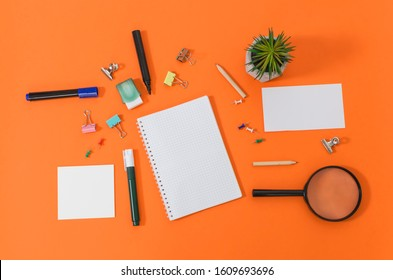 Close up office supplies on orange background, top of view
