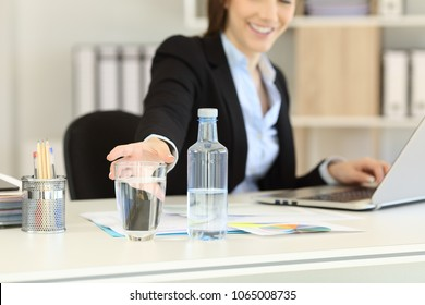 Close up of an office worker hand reaching a glass of bottled water