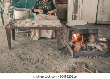 Close up of old Arab woman in Bedouin tent  kneading fresh dough for Taboon bread or Lafah is a Middle Eastern  flatbread also called lafa or Iraqi pita.Toned image.Real people.
