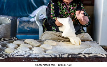 Close up of old Arab woman hands kneading fresh dough for Taboon bread or Lafah is a Middle Eastern  flatbread also called lafa or Iraqi pita.