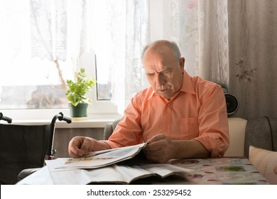 Close up Old Bald Man Reading News Updates on Tabloid While Sitting at the Living Room Near the Window.